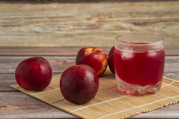 Rote pfirsiche mit einer tasse eisgetränk