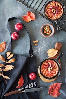 Rote pflaumen und pflaumentörtchen in gusseisernen pfannen auf einer schwarzen kochschürze, die auf grau geworfen wird