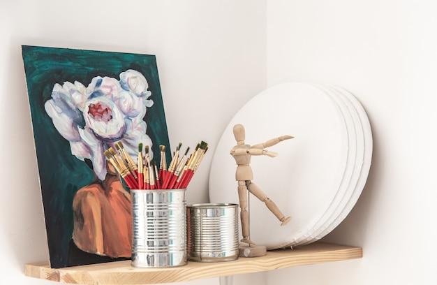 Rote pinsel zum malen in einer blechdose auf einem regal in einer werkstatt