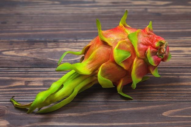 Rote pitahaya. reife pitahaya-frucht liegt auf einem hintergrund von holzbrettern