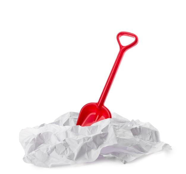 Rote plastikspielzeugschaufel in papier