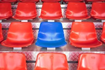 Rote Plastikstühle mit blauen Sitzen in der Mitte. Denken Sie an den Mut, anders zu sein.