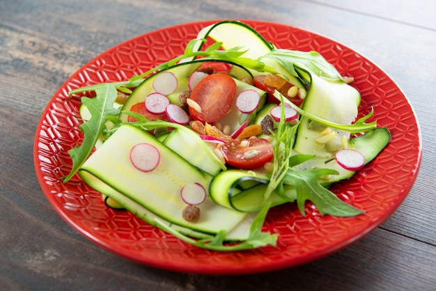 Rote platte mit vegetarischem salat des natürlichen organischen gemüses