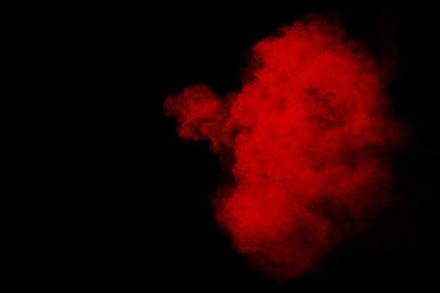 Rote pulverexplosionswolke auf schwarzem hintergrund.