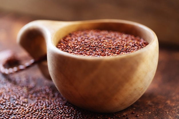Rote quinoakörner. samen der roten quinoa - chenopodium quinoa, in holzbecher