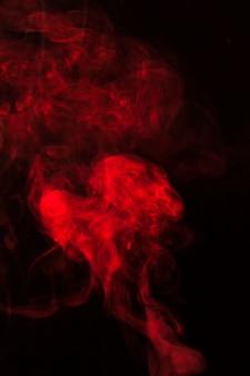 Rote rauchfragmente entwerfen auf einem schwarzen hintergrund