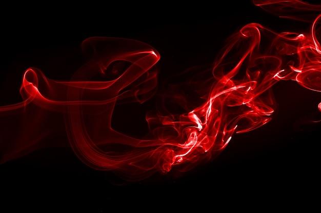 Rote rauchzusammenfassung auf schwarzem hintergrund. branddesign, dunkelheitskonzept
