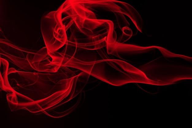 Rote rauchzusammenfassung auf schwarzem hintergrund, feuerdesign und dunkelheitskonzept