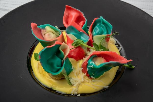 Rote ravioli mit pilzen serviert auf einem schwarzen teller auf einem holztisch