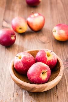 Rote reife äpfel in einer hölzernen platte und auf einer hölzernen tabelle