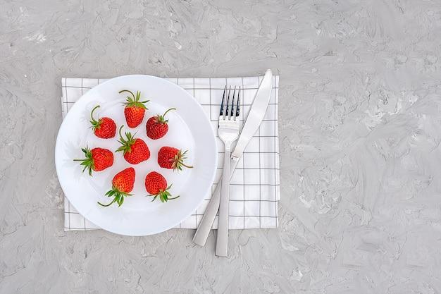 Rote reife erdbeerbeere auf weißer platte, tischbesteck und rotem wecker auf grauer steintabelle.