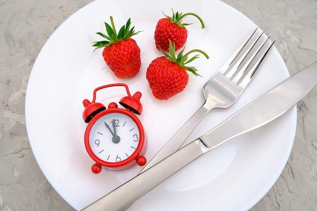 Rote reife erdbeerbeere auf weißer platte