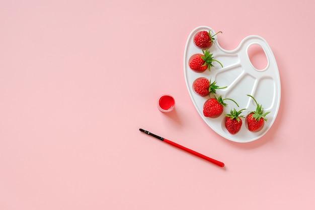 Rote reife erdbeeren auf künstlerischer palette