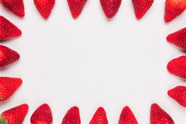 Rote reife erdbeeren im rahmen auf weißem hintergrund