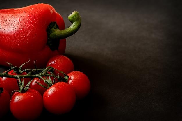 Rote reife frische kirschtomaten auf zweig und pfeffer auf dunkler oberfläche. gesundes essen und diät