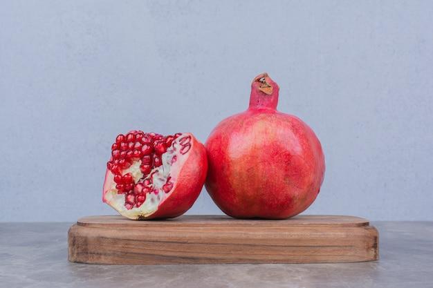 Rote reife granatäpfel auf holzbrett.
