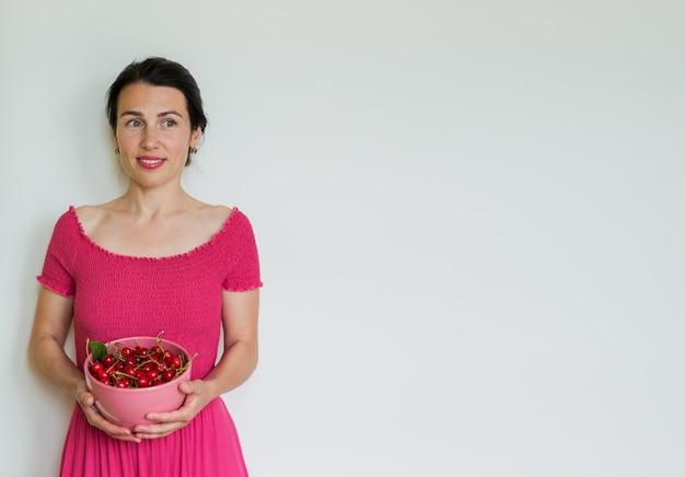 Rote reife kirschen in der schüssel in den händen der frau. gesunde ernährung, vegetarisches essen und diät menschen konzept