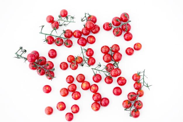 Rote reife kirschtomaten auf einer weißen oberfläche