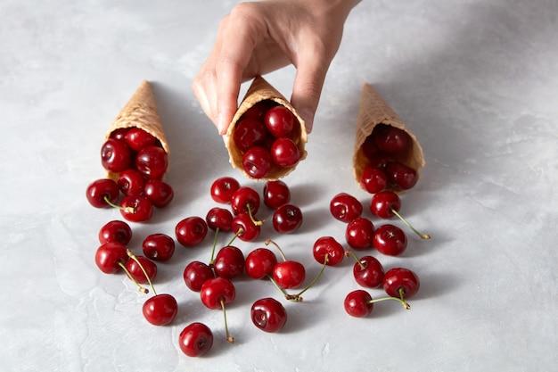 Rote reife saftige kirschen an den waffelkegeln