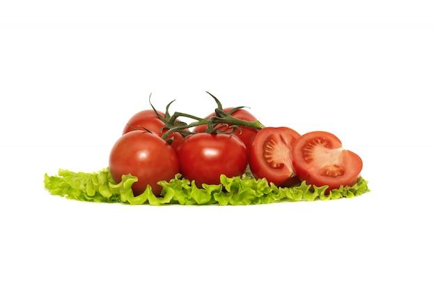 Rote, reife tomaten auf einem frischen salatblatt, lokalisiert auf weiß