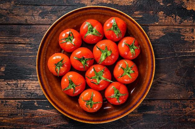 Rote reife tomaten auf rustikalem teller. dunkler hölzerner hintergrund. draufsicht.