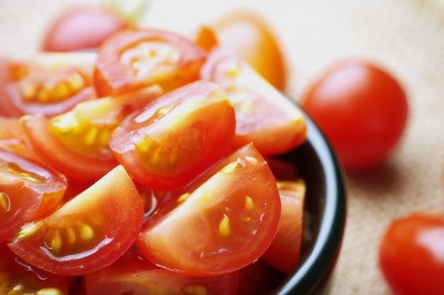 Rote reife tomaten geschnitten in einer schwarzen schüssel