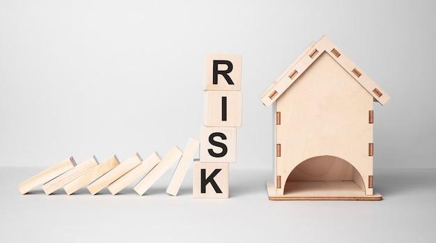 Rote risiko-würfelblöcke stoppen fallende blöcke und schützen die hausminiatur. herbst business, hausratversicherung, investitionen, krise, wirtschaftsrezession
