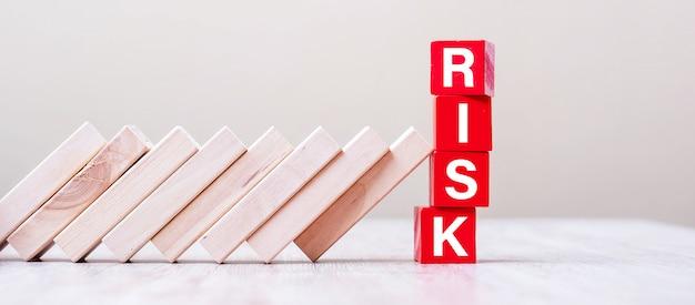 Rote risiko-würfelblöcke verhindern, dass blöcke auf den tisch fallen. herbst geschäfts-, planungs-, management-, lösungs-, versicherungs- und strategiekonzepte