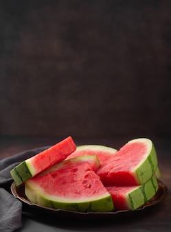 Rote rohe wassermelonenstücke auf dunklem hintergrund