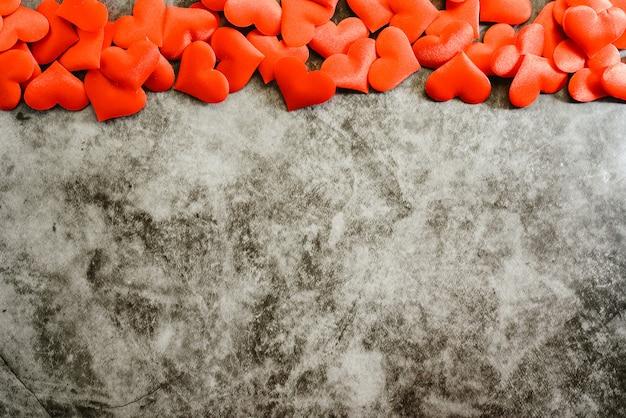 Rote romantische herzen, die einen strukturierten marmorhintergrund für gebrauch am valentinstag gestalten