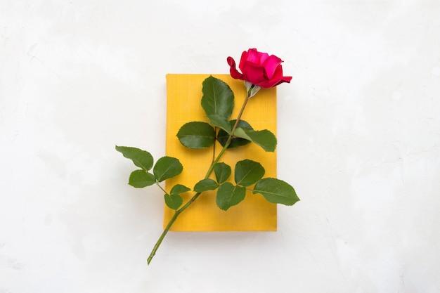 Rote rose auf einem buch mit gelbem umschlag auf hellem steinhintergrund. das konzept der romantischen literatur. flache lage, draufsicht