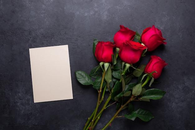 Rote rose blüht blumenstrauß auf schwarzem stein. draufsicht der valentinstaggrußkarte