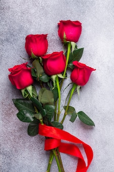 Rote rose blüht blumenstrauß auf stein. valentinstag