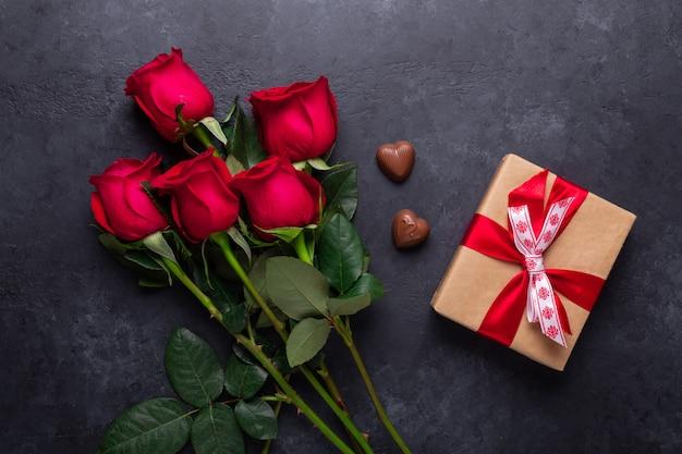 Rote rose blüht blumenstrauß, geschenkbox, schokoladenbonbons auf schwarzem stein. valentinstag-grußkarte