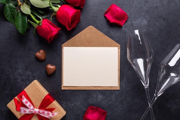 Rote rose blüht blumenstrauß, umschlag, geschenkbox, schokoladenbonbons, champagnergläser auf schwarzem stein. hintergrund copyspace