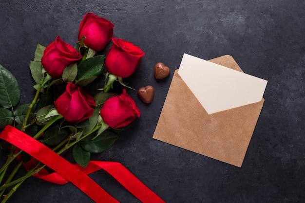 Rote rose blüht blumenstrauß, umschlag, schokoladenbonbons auf schwarzem stein. valentinstag-grußkarte