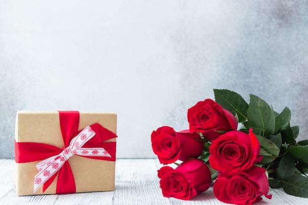 Rote rose blüht blumenstrauß und geschenkbox auf stein. valentinstag-grußkarte