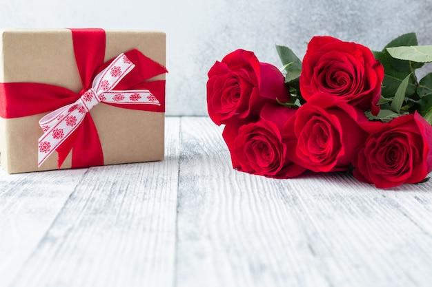 Rote rose blüht blumenstrauß und geschenkbox auf stein. valentinstag