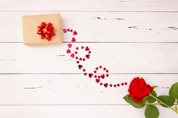 Rote rose, geschenkbox und herzen auf hölzernem hintergrund