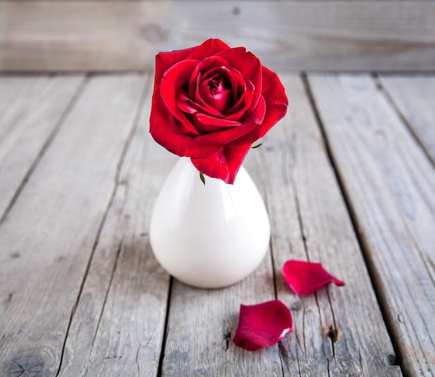 Rote rose in der vase auf holztisch