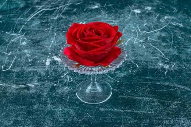 Rote rose in einem glassockel auf blauem hintergrund.