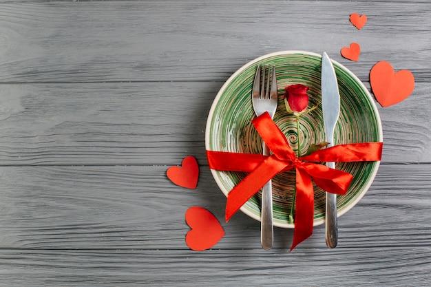 Rote rose mit besteck auf schüssel