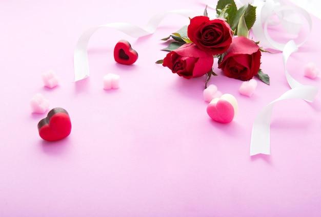 Rote rose mit gekräuseltem weißem band auf hellrosa hintergrund.