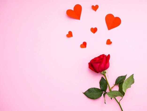 Rote rose mit rotem papier des herzens