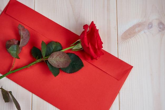Rote rose, roter umschlag auf einem hellen hölzernen hintergrund