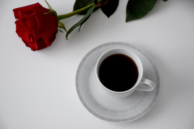 Rote rose, tasse kaffee auf teller mit grauem tee auf weißem tisch. valentinstag frühstück.