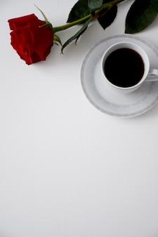 Rote rose, tasse kaffee auf teller mit grauem tee auf weißem tisch. valentinstagskarte