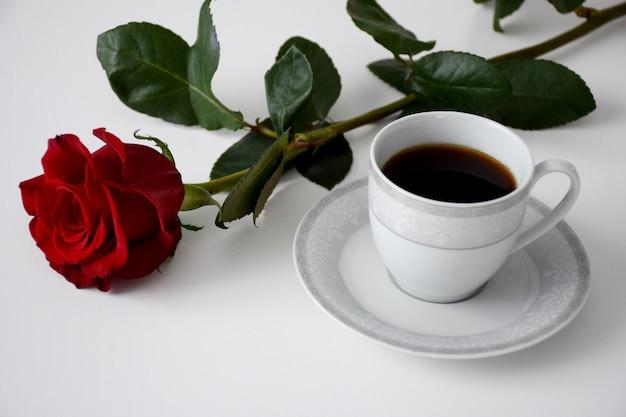 Rote rose, tasse tee auf teller mit grauem tee auf weißem tisch. valentinstag kaffee