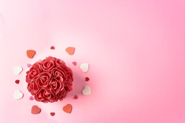 Rote rose, umgeben von schaumherzen für valentinstag in einem rosa hintergrund