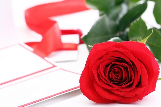 Rote rose und feiertagsumschlag